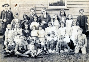 Christmas Hills State School, 1911, with five-year-old Phil Britton (arrowed) front row at left. The teacher pictured is probably Fred Parsons. The original school was a room provided by Tommy and Lizzie Hine, who also lodged the teacher and kept the post office. This was a 'subsidised' school, which relied upon the regular attendance of a set number of students and the community providing suitable lodgings for the teacher.
